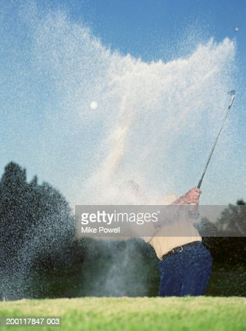 Man chipping golf ball out of bunker, sand flying