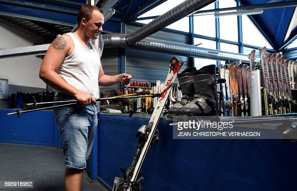 A man chooses his ski equipment at the Snowhall the only indoor ski run in France in Amneville eastern France on August 26 2016 as a heatwave strikes...