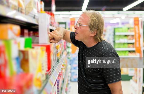 Mann entscheidet sich für Produkte im Supermarkt