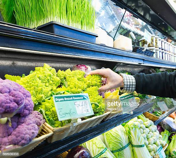 Man choosing broccoli in supermarket