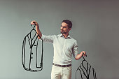 Handsome man in smart casual wear is holding drawn men suits and choosing between, on gray background