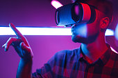 Young man in VR goggles choosing options while having virtual reality experience in room with neon lights.