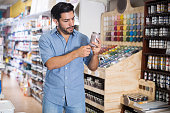 Handsome concentrated young man choosing paints in hardware store
