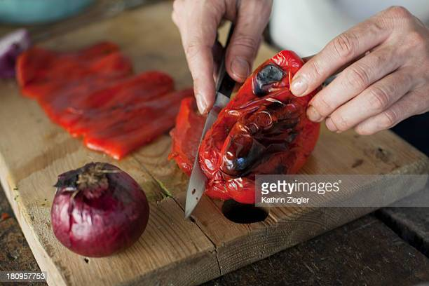 Man chopping and skinning roasted bell pepper