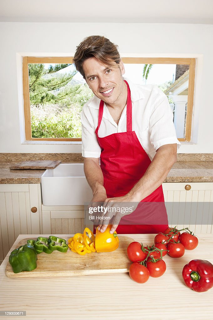 Man chopping vegetables in kitchen : Stock Photo