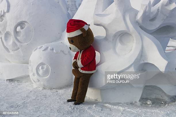 A man clad in a teddy bear suit leans on a snow sculpture during the 16th Harbin International Ice and Snow Festival in Harbin northeast China's...