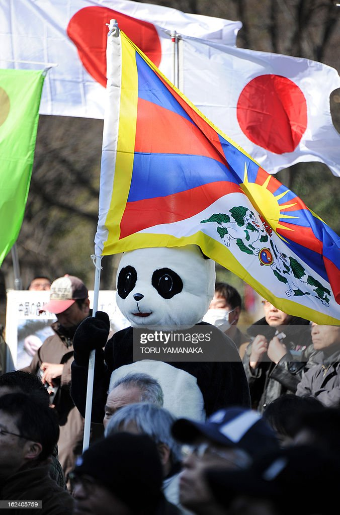 A man clad in giant panda costume, holds a Tibetan flag in front of Japanese national flags during a rally denouncing China organized by a Japanese nationalist group in Tokyo on February 23, 2013. Several hundred people took part in the event. AFP PHOTO/Toru YAMANAKA
