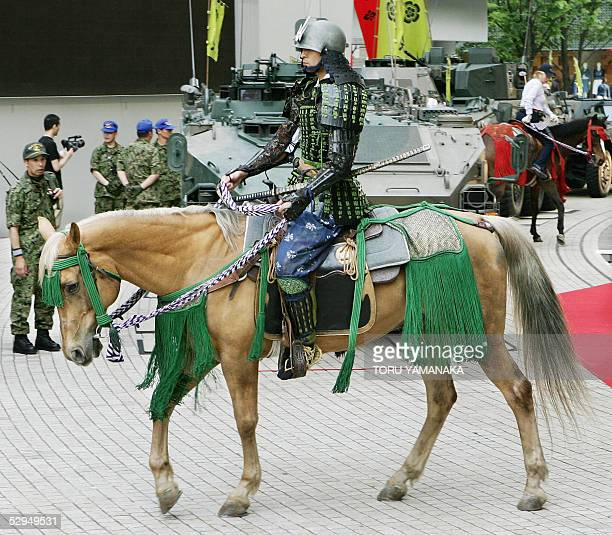 A man clad in samurai armour rides horseback before soldiers and armored personnel carriers of the Japan's Ground SelfDefense Force before a...