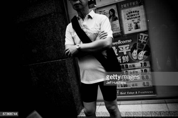 A man clad in spandex shorts a man waits for a bus on October 24 2005 in Hong Kong China