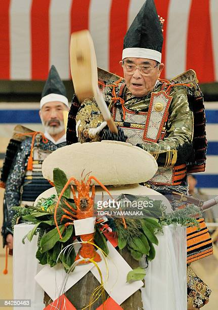 A man clad in traditional 'samurai' armour tries to smash big rice cakes with a wooden hammer to celebrate the new year during the Japanese martial...