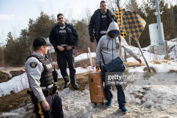 A man claiming to be from Sudan is met by Royal Canadian Mounted Police officers after he crossed the USCanada border into Canada February 22 2017 in...