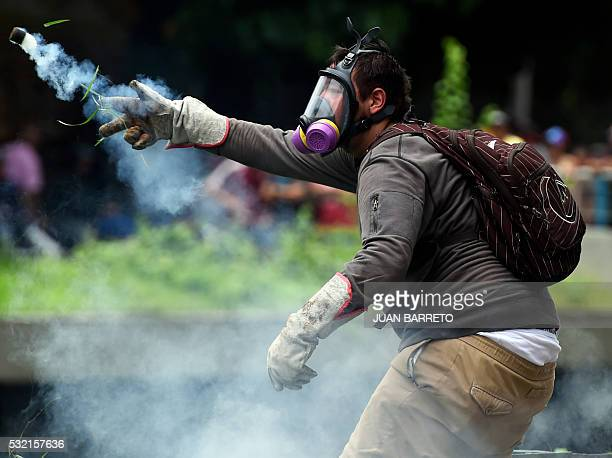 TOPSHOT A man clashes with policemen during a protest against new emergency powers decreed this week by President Nicolas Maduro in Caracas on May 18...