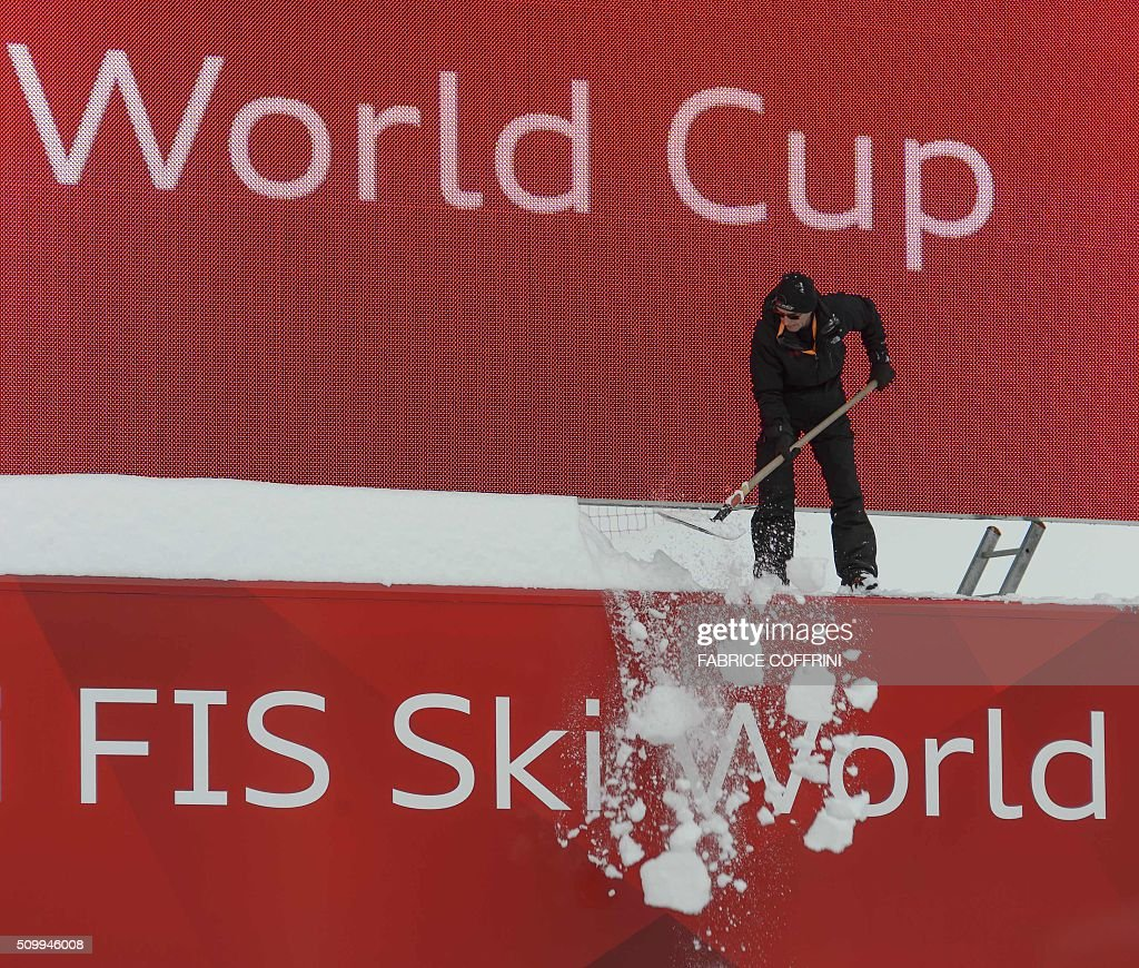 A man clean a giant TV board at the FIS Alpine Skiing World Cup in Crans-Montana on February 13, 2016. The women's downhill race has been delayed to February 14, 2016 due to the major snowfall. / AFP / FABRICE COFFRINI