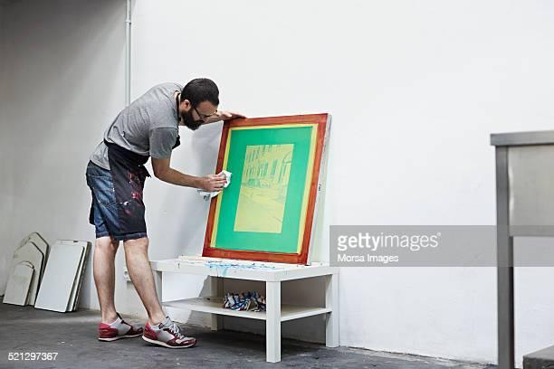 Man cleaning a silk screen