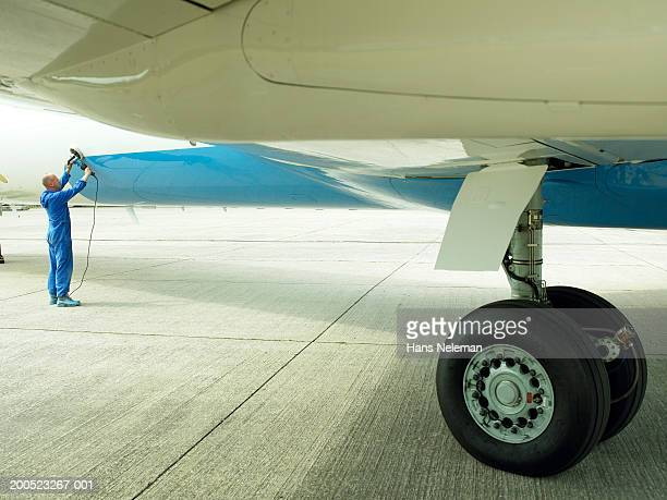 Man cleaning aircraft, outdoors