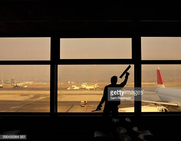 Man cleaning airport windows, facing runway, rear view