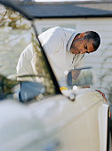 Man cleaning car parked outside house
