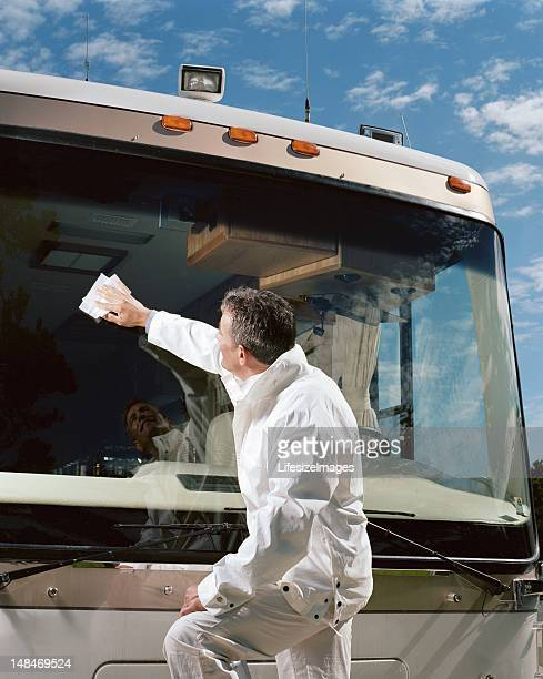 Man cleaning coach bus windshield, side view