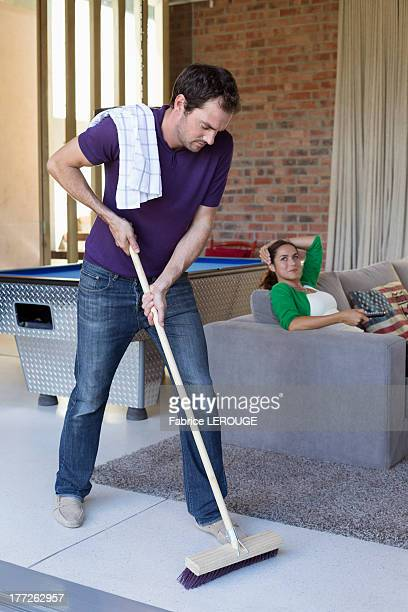 Man cleaning floor with a mop and his wife watching television in the background