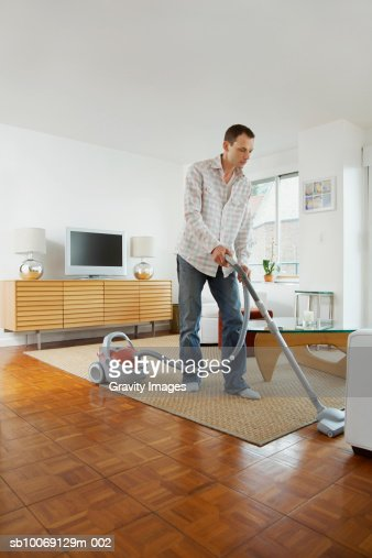 Man cleaning floor with vacuum cleaner : Stock Photo
