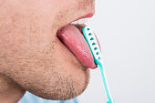 Close-up Of Young Man Cleaning His Tongue With Scraper