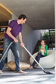 Man cleaning house with a vacuum cleaner with his wife sitting on a seat