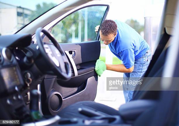 Man cleaning interior of his car.