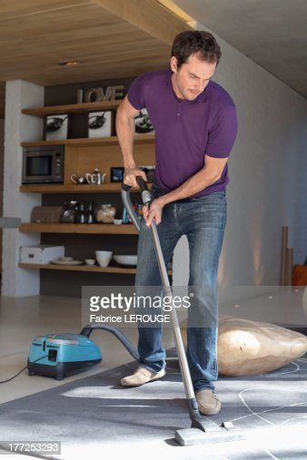 Man cleaning living room with vacuum cleaner