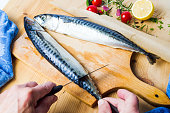 Man cleaning fresh mackerel fish first person view