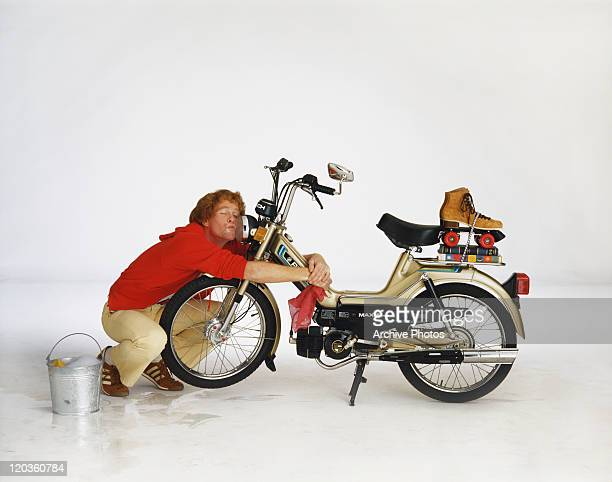 Man cleaning motorbike on white background