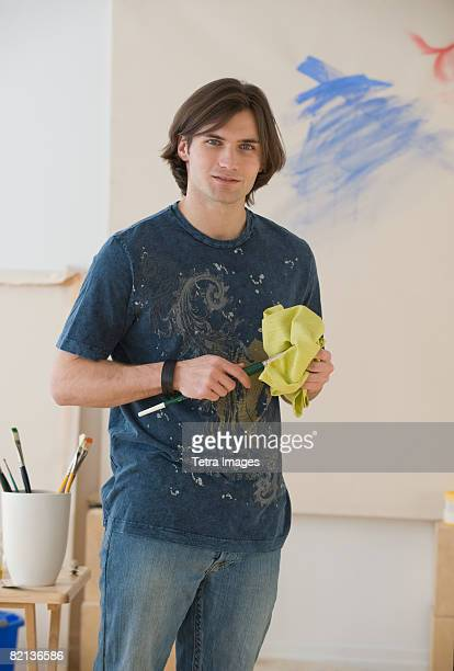 Man cleaning paintbrush in front of easel