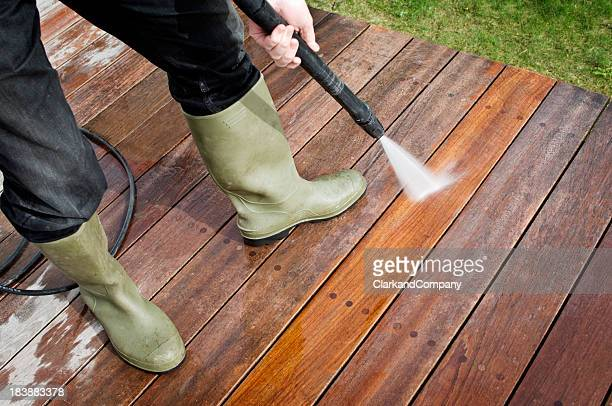 Man Cleaning Patio Decking With a Pressure Hose