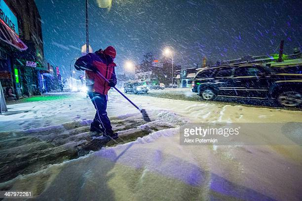 Man cleaning street from the snow under blizzard