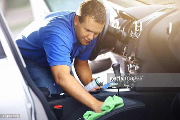 Homme nettoyage tissus d'ameublement de son véhicule.
