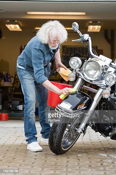 Man cleaning vintage motorbike in driveway