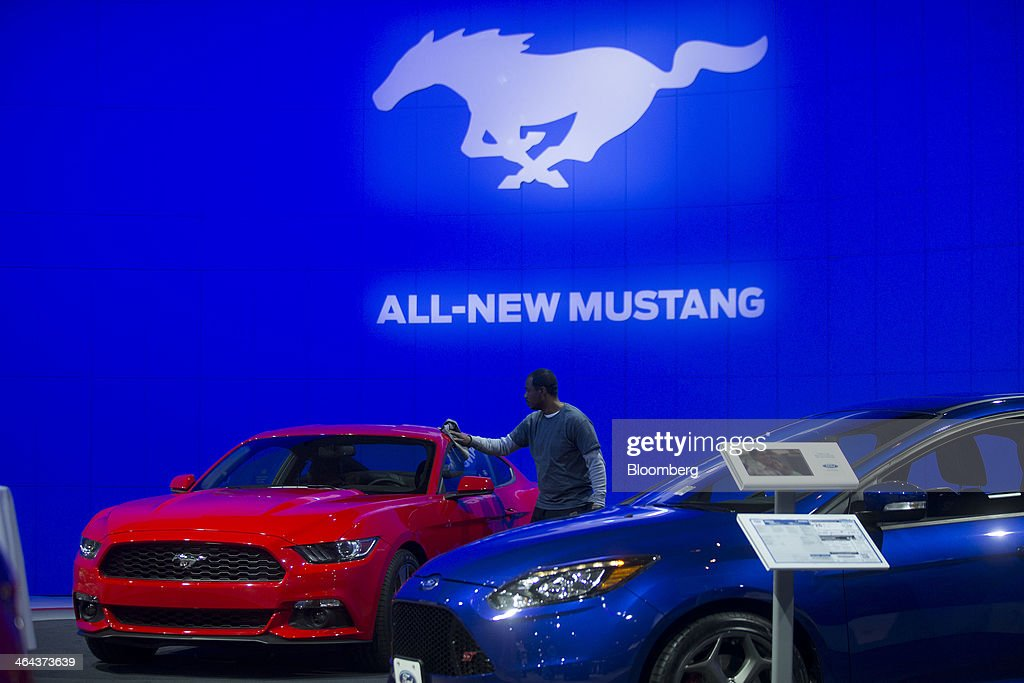 A man cleans a 2015 Ford Motor Co. Mustang during the Washington Auto Show in Washington, D.C., U.S., on Wednesday, Jan. 22, 2014. After laboring for five years to develop its aluminum F-150, Ford Motor Co. now confronts a new challenge: preventing higher insurance rates and a dearth of mechanics equipped to repair its body from deterring buyers. Photographer: Andrew Harrer/Bloomberg via Getty Images