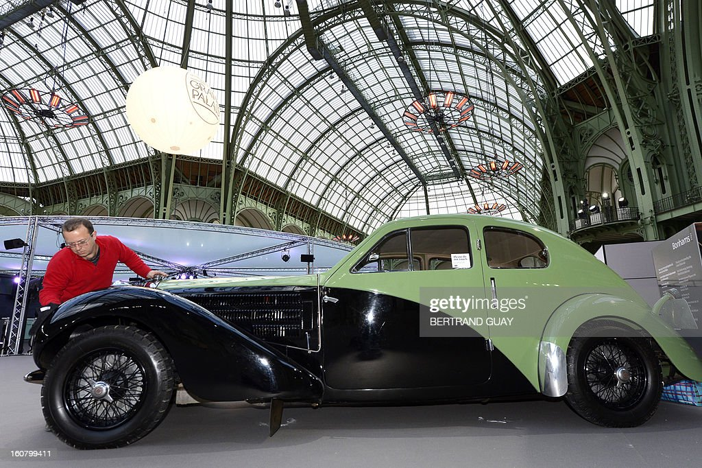 A man cleans a Bugatti type 57C Ex (1938) as luxury vintages cars are displayed at an auction at the Grand Palais on February 6, 2013 in Paris. 125 vintage motor cars, 100 collection motorbikes and a 1920's Gipsy Moth plane by De Havilland, will be presented at the Bonhams auction on February 7.