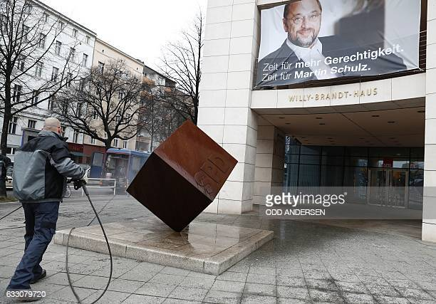 A man cleans a cube sculpture with the logo of Germany's Social Democratic Party in front of the party's headquarters in Berlin where former European...