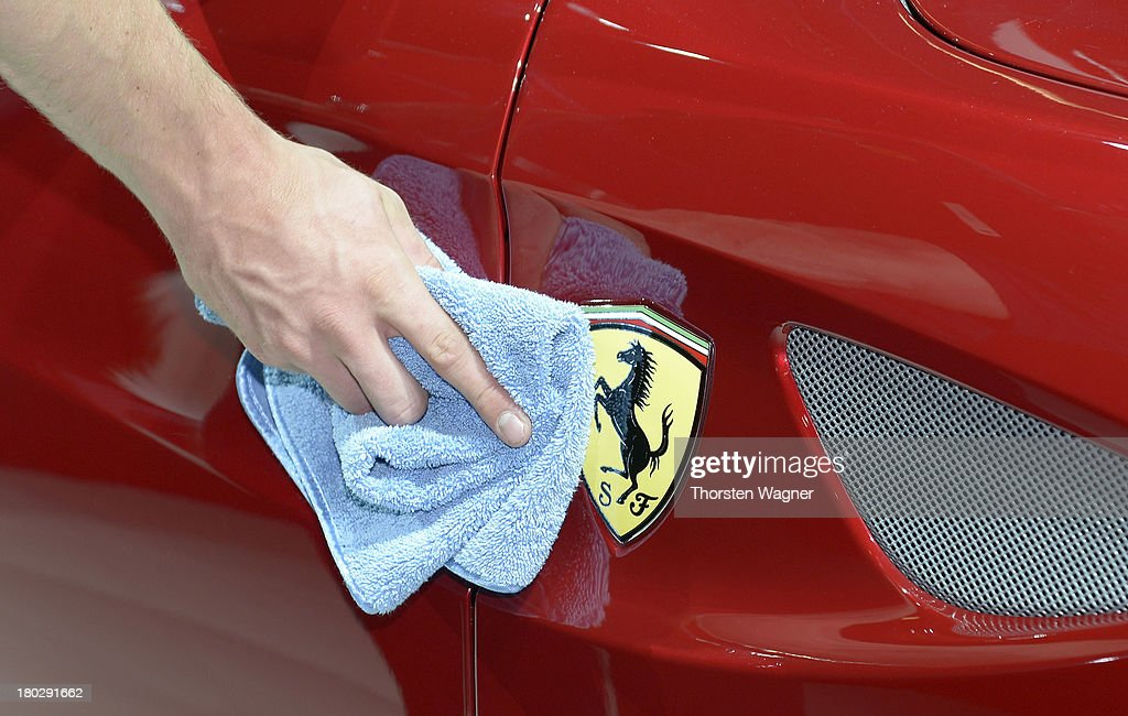 A man cleans a Ferrari logo during the press day at the international motor show IAA (Internationale Automobil-Ausstellung) on September 11, 2013 in Frankfurt am Main, Germany. The world's biggest motor show, the IAA, is running from September 12 to 22, 2013