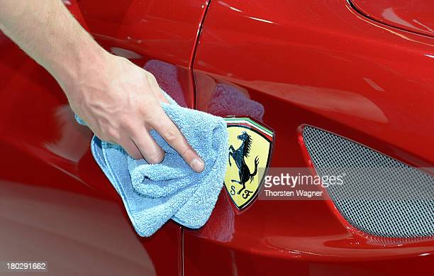 A man cleans a Ferrari logo during the press day at the international motor show IAA on September 11 2013 in Frankfurt am Main Germany The world's...