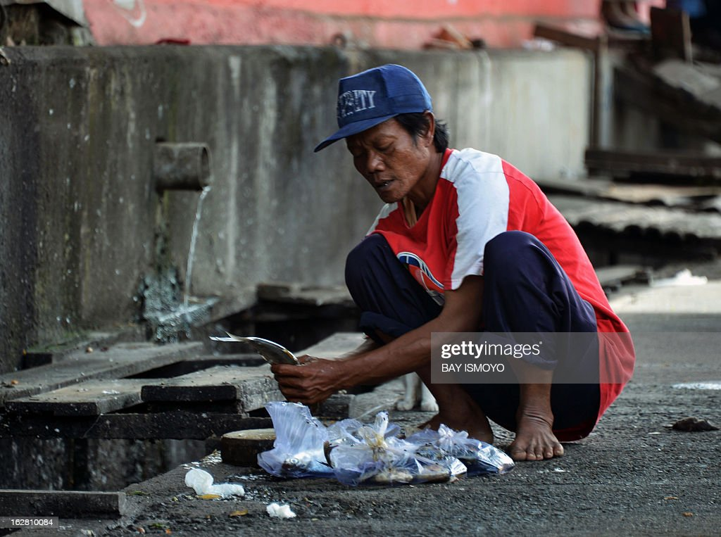 A man cleans a fish next to a waste water hose in Jakarta on February 28, 2013. The government statistics show that the decrease in the official poverty rate is slowing — from 12.3 percent of all Indonesians in September 2011 to 11.7 percent a year later and in a speech to district leaders last week, Indonesian President Susilo Bambang Yudhoyono said job creation was the most effective way to reduce poverty. AFP PHOTO / Bay ISMOYO
