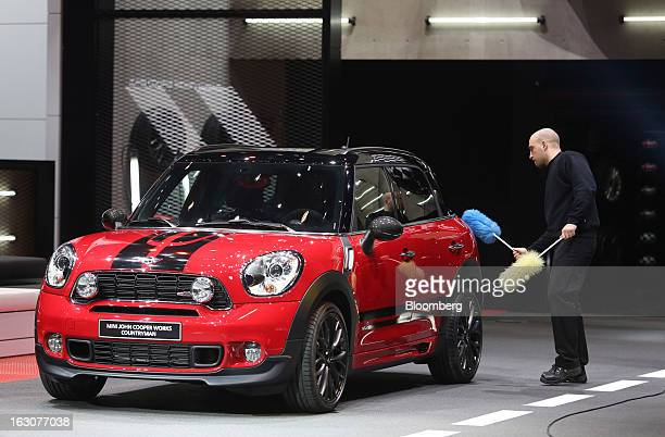 A man cleans a Mini John Cooper Works Countryman automobile produced by Bayerische Motoren Werke AG as it sits on the company's stand ahead of the...