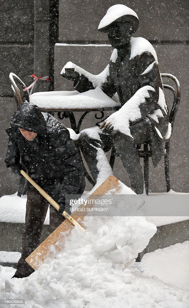 A man cleans a snow in front of a monument during a heavy snow fall in Kiev on January 31, 2013.
