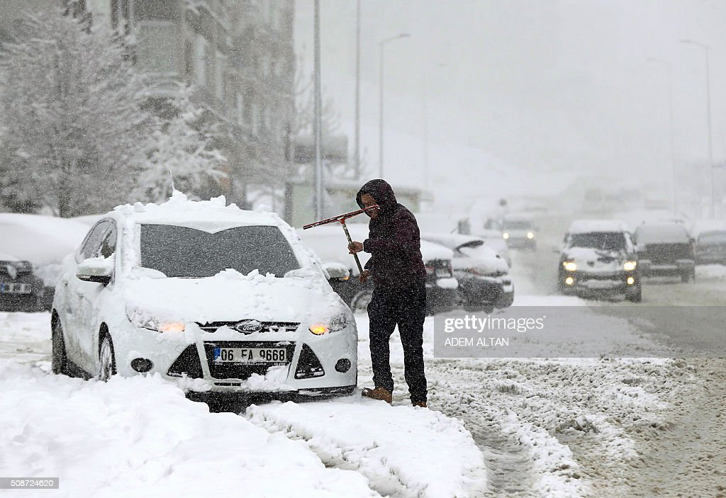 A man cleans a snow-covered car by the streets where motorists drive under the snow in Ankara on February 6, 2016. / AFP / ADEM ALTAN