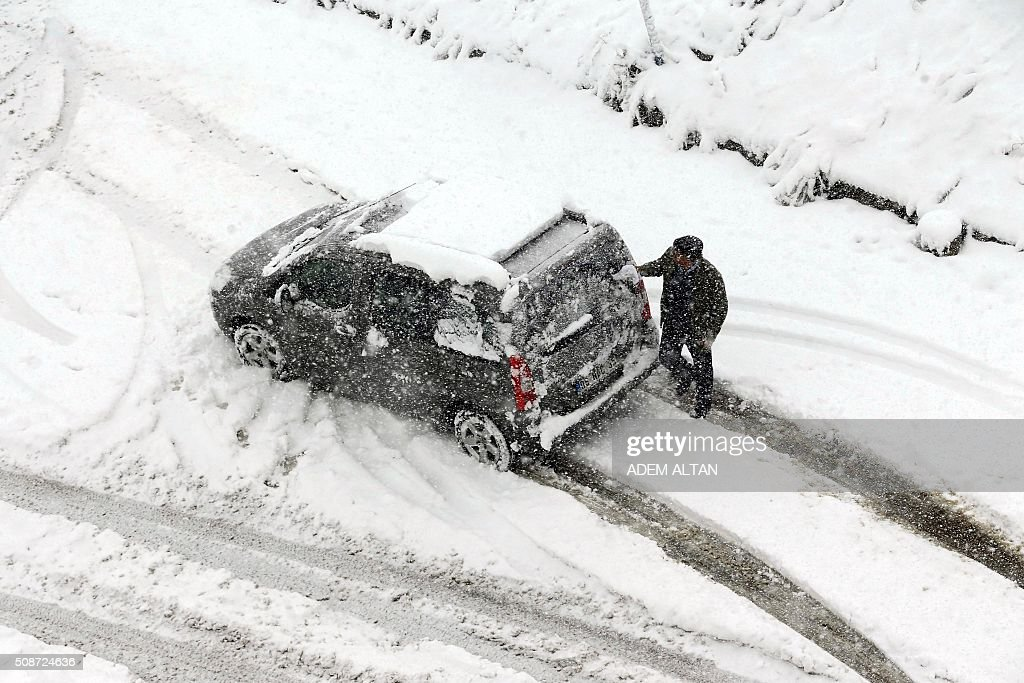 A man cleans a snow-covered car under the snow in Ankara on February 6, 2016. / AFP / ADEM ALTAN