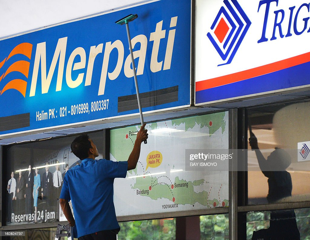 A man cleans billboards in Jakarta on February 28, 2013. Indonesia said that growth in Southeast Asia's biggest economy slowed to 6.23 percent in 2012 owing to global headwinds, but was supported by strong domestic consumption and investment. AFP PHOTO / Bay ISMOYO