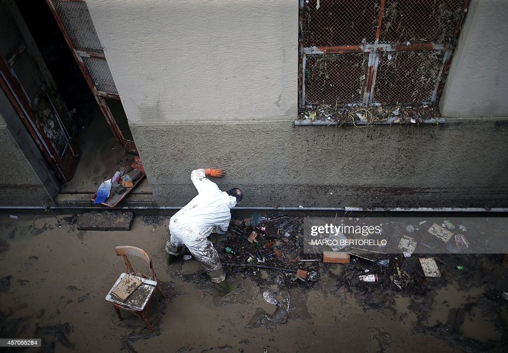 A man cleans his flooded home in downtown Genoa on October 11 a day after one person died when flood waters swept through the city following...