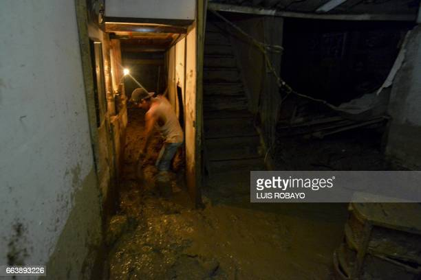 A man cleans mud out of his house damaged by mudslides following heavy rains in Mocoa Putumayo department southern Colombia on April 2 2017 The death...