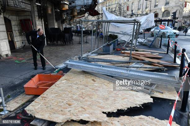 A man cleans rubbles next to a scaffolding which felt down following strong winds on February 4 in Bordeaux southwestern France / AFP / GEORGES GOBET