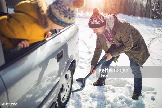 Man cleans snow near the car  in nature